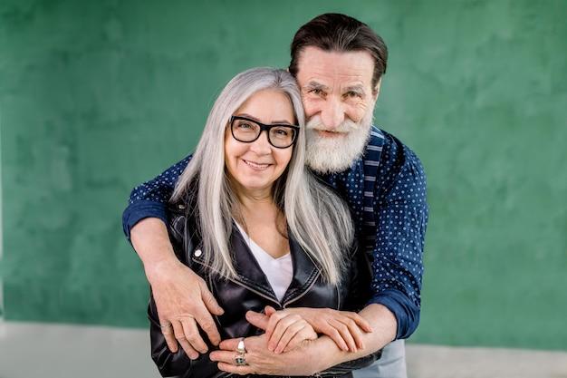 Allegro uomo barbuto elegante che abbraccia la moglie dai capelli grigi da dietro e guardando la telecamera