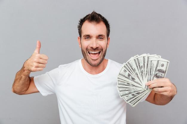 Allegro giovane di successo che tiene soldi e mostra i pollici su sfondo grigio