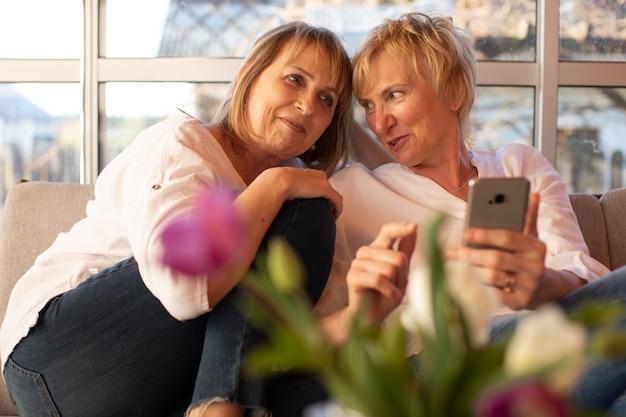 Serata estiva allegra di due amiche di 55 anni sulla veranda di una casa di legno, usa uno smartphone, una conversazione confidenziale