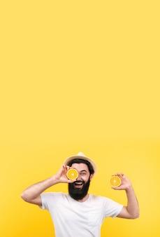 Allegro uomo estivo in cappello di panama con frutta arance, immagine mock-up con posto per il testo