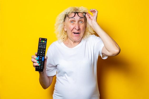 Donna anziana bionda sorpresa allegra in vetri che tengono un telecomando