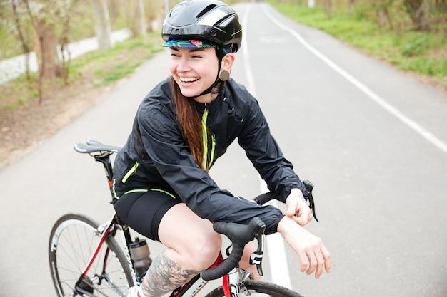 Allegra giovane donna tatuata in casco protettivo in bicicletta in piedi sulla strada
