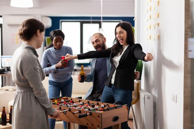 Un'allegra squadra di colleghi multietnici si diverte con il calcio balilla. attività vincente di donna felice mentre gli amici si siedono con tazze di bottiglie di birra. festa dopo il lavoro