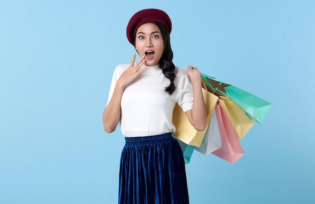 Allegra donna asiatica adolescente che si gode lo shopping, sta portando borse della spesa e sorpresa al centro commerciale.