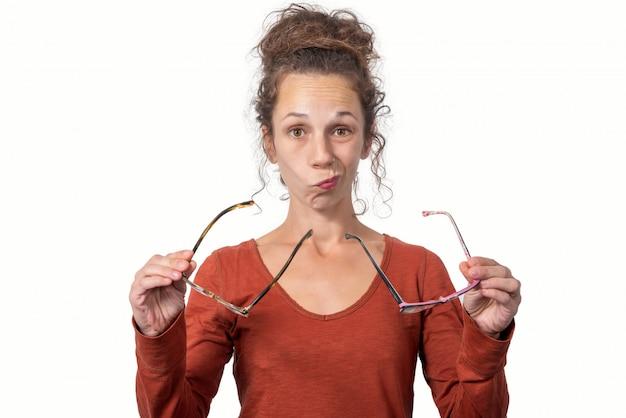 Ragazza alla moda allegra che ha difficoltà a scegliere gli occhiali