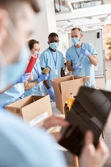 Volontari allegri in maschere e guanti protettivi uniformi blu che smistano l'imballaggio di cibo dentro