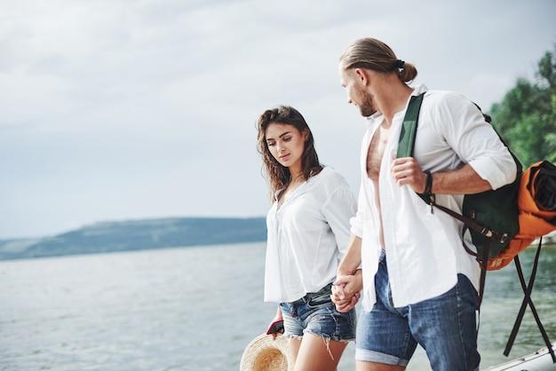Passeggiata allegra di coppia adorabile all'aperto sullo sfondo del lago.