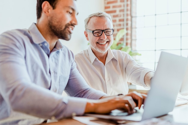 Sviluppatori web allegri che lavorano su un laptop