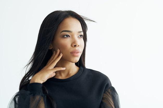 Cosmetici del primo piano del viso dei capelli neri lunghi dell'aspetto africano della donna allegra