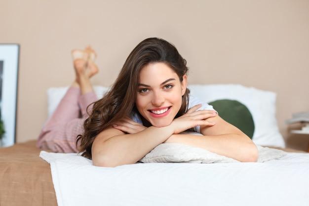 La donna allegra sul letto sta sorridendo e sta esaminando la macchina fotografica.