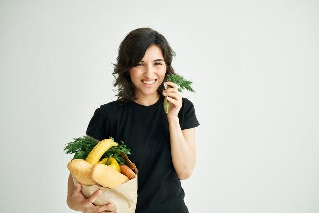 Donna allegra in maglietta nera con un pacchetto di generi alimentari del supermercato
