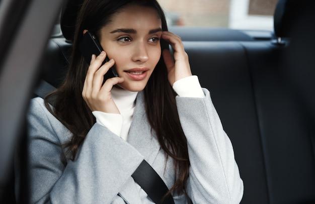 Donna allegra in vestito di affari che si siede sul sedile posteriore della sua auto e parla al telefono cellulare