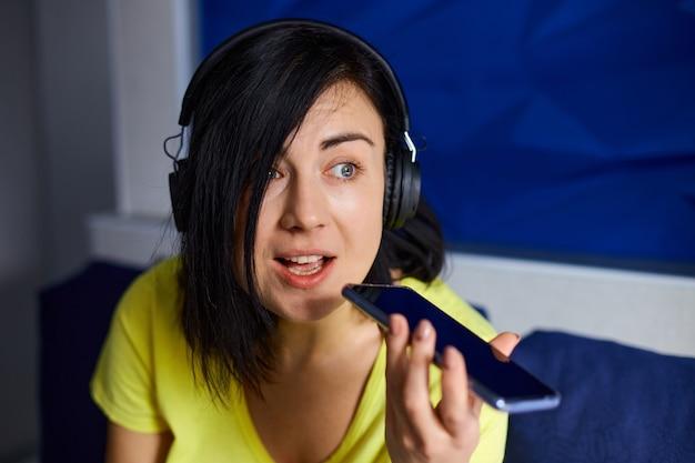 Donna allegra in abiti casual con cuffie e smartphone, registra per podcast sul divano di casa.