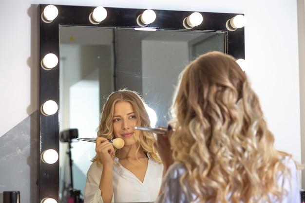 Cliente donna allegra che guarda il suo riflesso nello specchio e corregge il trucco con un pennello al salone di bellezza