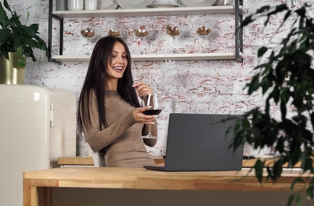Donna allegra che beve vino durante l'utilizzo di laptop per videochiamata