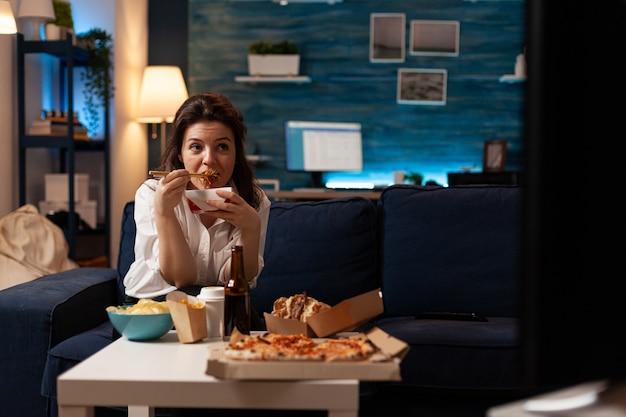 Donna allegra che mangia cibo cinese gustoso che si rilassa sul divano