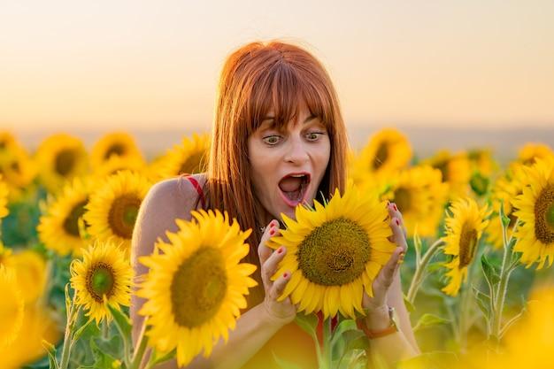 Donna allegra che si gode la giornata in un campo di girasoli e guarda un girasole.