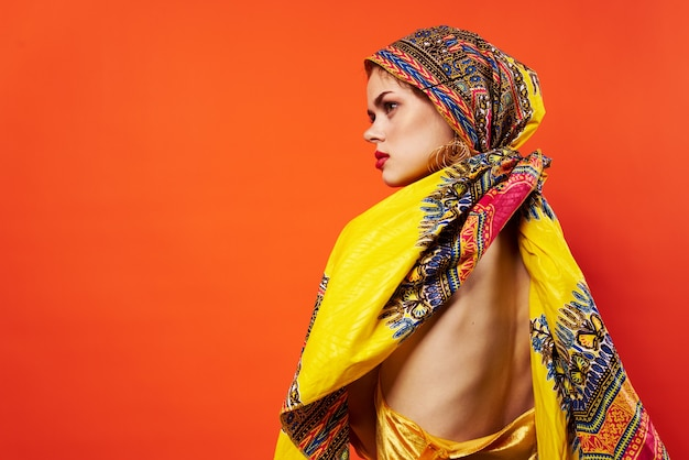 Donna allegra etnia multicolore foulard trucco glamour sfondo rosso
