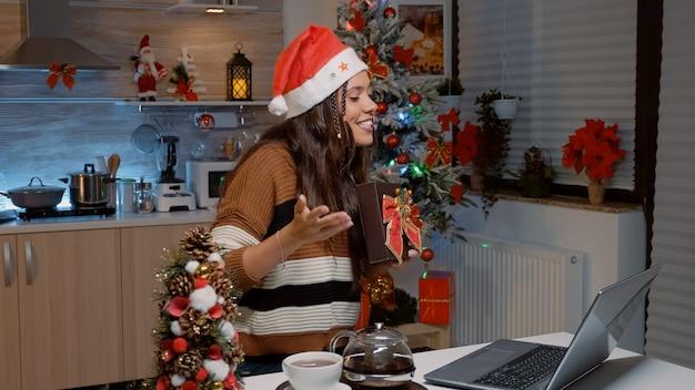 Donna allegra che scambia regali durante una videochiamata con laptop
