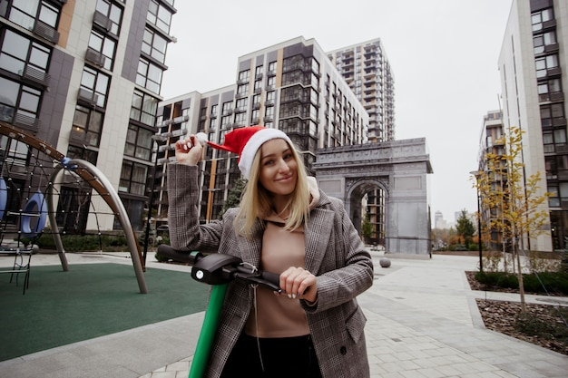 Donna allegra che fissa il cappello di babbo natale e guida lo scooter elettrico. blocchi di appartamenti sullo sfondo. una donna felice si è acquistata uno scooter elettrico in onore delle vacanze di natale.