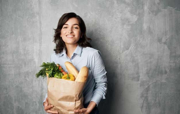 Donna allegra dalla consegna del supermercato dello shopping del pacchetto di cibo sano