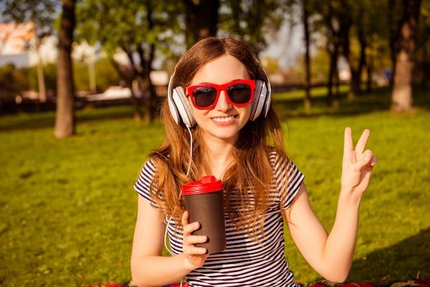Donna allegra in bicchieri ascoltando musica e gesticolando mentre beve il caffè nel parco