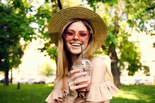Donna allegra in un cappello e occhiali con un bicchiere di bevanda d'aria fresca. foto di alta qualità