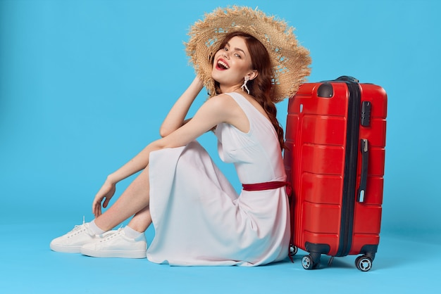 Una donna allegra con un cappello si siede sul pavimento con una destinazione di viaggio in valigia