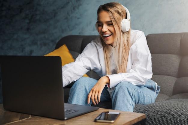Donna allegra in cuffie che si siede sul divano davanti al computer portatile e guardare video divertenti