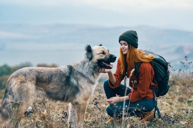 Viandante della donna allegra cammina il cane sulla natura nel paesaggio delle montagne