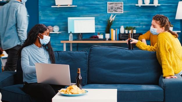 Donna allegra che tiene in mano una bottiglia di birra guardando il computer portatile che discute con un amico africano in soggiorno indossando una maschera facciale per prevenire la diffusione del coronavirus in tempo di pandemia globale