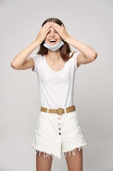 Donna allegra che tiene una faccia della mascherina medica della maglietta bianca