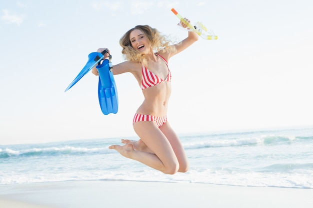 Donna allegra che salta sulla spiaggia