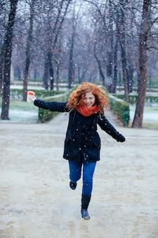 Donna allegra che salta sulle pozzanghere sotto la neve nel parco