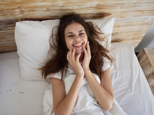 La donna allegra si trova a letto, sorride la gioia mattutina