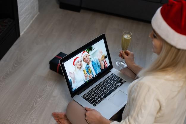 Donna allegra che fa una videochiamata il giorno di natale e saluta qualcuno, sembra felice, stringe il pugno come un vincitore, guarda lo schermo del dispositivo, posa al coperto vicino al camino