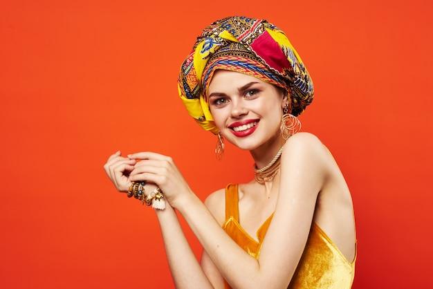 Donna allegra in turbante multicolore aspetto attraente gioielli sfondo isolato