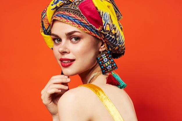 Donna allegra in aspetto attraente turbante multicolore sfondo rosso gioielli. foto di alta qualità