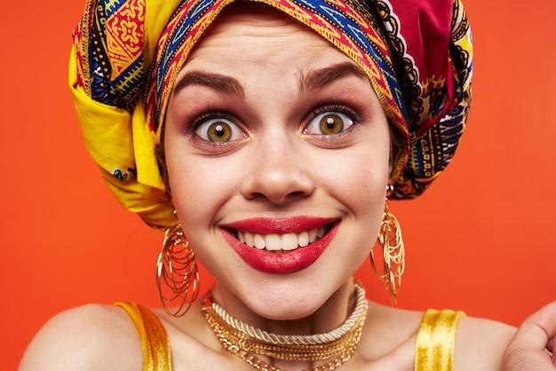 Donna allegra in turbante multicolore aspetto attraente gioielli sfondo rosso