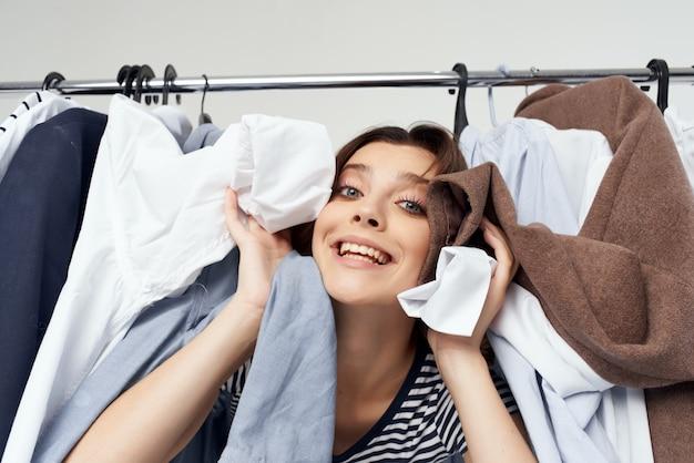 Donna allegra vicino allo sfondo isolato shopping maniaco del guardaroba