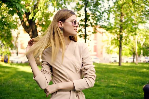 Donna allegra nella passeggiata estiva dell'erba verde del parco