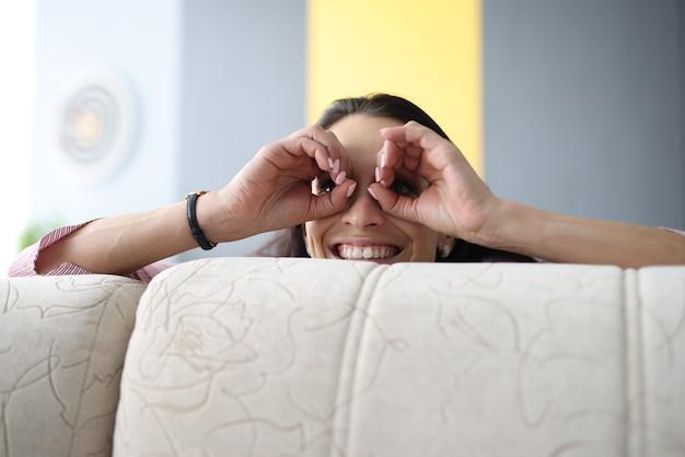 Donna allegra sbirciare da dietro il divano