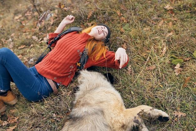 Donna allegra che gioca con il viaggio nella natura del cane
