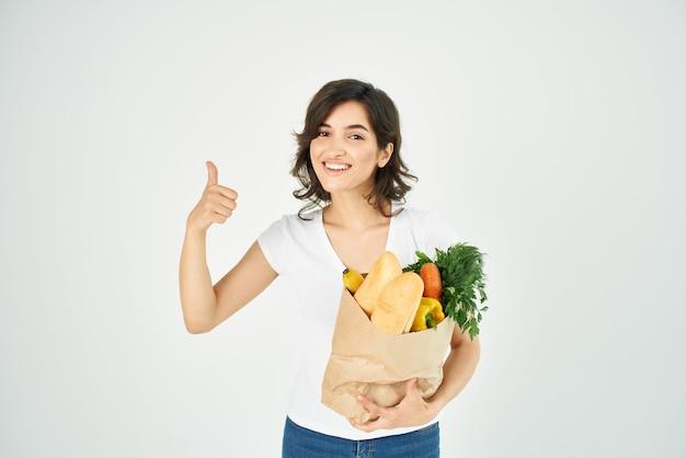 Donna allegra positivo stesso pacchetto stringa con generi alimentari nella consegna del supermercato