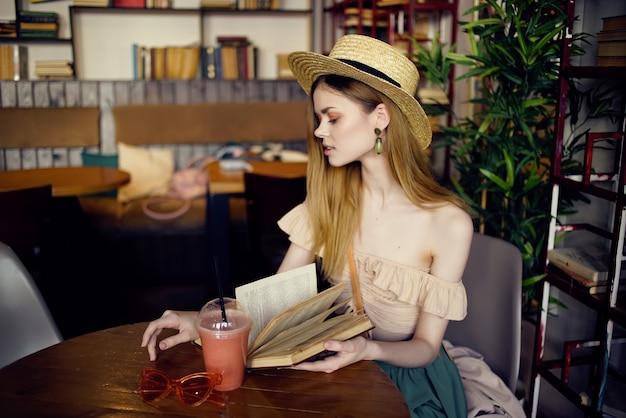 Donna allegra che legge un libro alla moda di un caffè