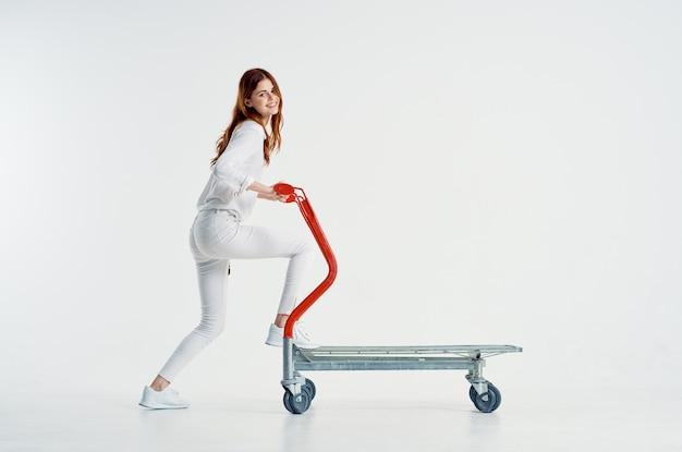 Donna allegra che guida la carrozza del carrello del supermercato