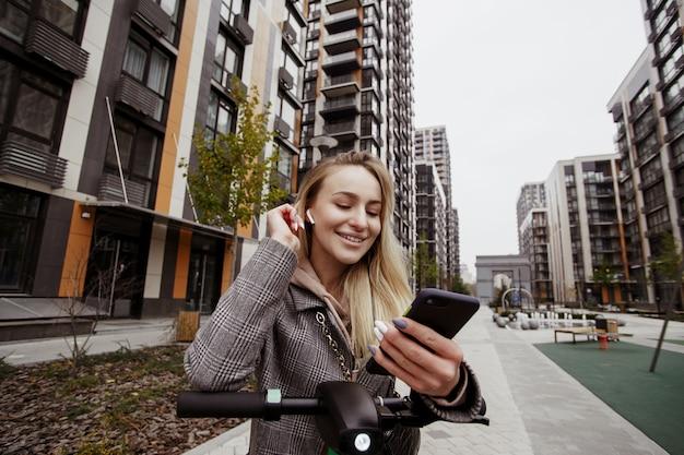 Donna allegra su scooter che indossa un cappotto accogliente casual, aggiustandosi i capelli e chiacchierando dal suo smartphone con servizio di noleggio di trasporto elettrico. blocchi di appartamenti sullo sfondo. buon concetto di servizio.