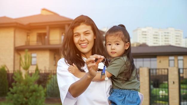 La donna allegra mostra le chiavi dell'appartamento che tiene la figlia