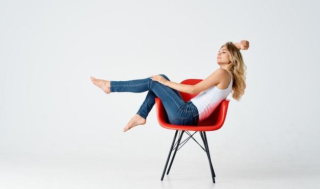 Donna allegra seduta su una sedia rossa con le gambe alzate divertimento a piedi nudi
