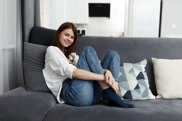 Donna allegra che si siede su un divano con resto piatto gambe sollevate.